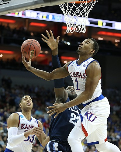Kansas guard Wayne Selden Jr. (1) is fouled on the way to the bucket by Villanova forward Daniel Ochefu (23) during the first half, Saturday, March 26, 2016 at KFC Yum! Center in Louisville, Kentucky. At left is Kansas forward Landen Lucas (33).
