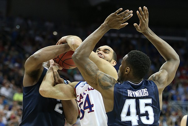 Kansas forward Perry Ellis (34) gets tied up with Villanova forward Kris Jenkins (2) and forward Darryl Reynolds (45) during the first half, Saturday, March 26, 2016 at KFC Yum! Center in Louisville, Kentucky.