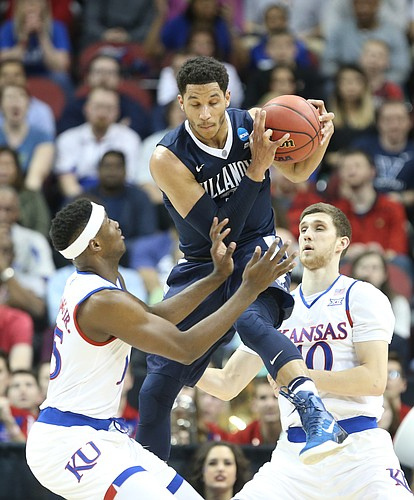 Villanova guard Josh Hart pulls down a rebound between Kansas forward Carlton Bragg Jr. (15) and guard Sviatoslav Mykhailiuk (10) during the first half, Saturday, March 26, 2016 at KFC Yum! Center in Louisville, Kentucky.