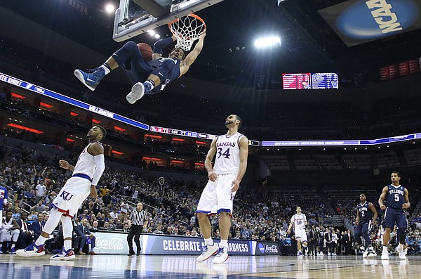 Villanova guard Josh Hart (3) hangs on the rim before Kansas forward Perry Ellis (34) and guard Frank Mason III (0) after a dunk during the first half, Saturday, March 26, 2016 at KFC Yum! Center in Louisville, Kentucky.