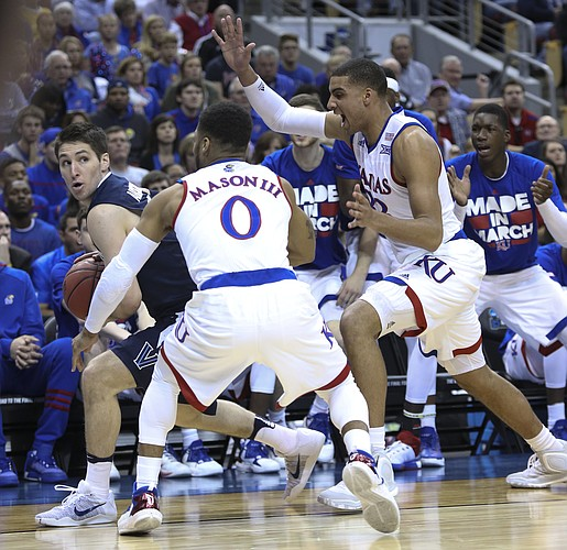 Kansas guard Frank Mason III (0) and Kansas forward Landen Lucas (33) trap Villanova guard Ryan Arcidiacono (15) in the Jayhawks' game against the Villanova Wildcats, Saturday, March 26, 2016 in an NCAA Elite Eight matchup at KFC YUM! Center in Louisville, Kentucky.
