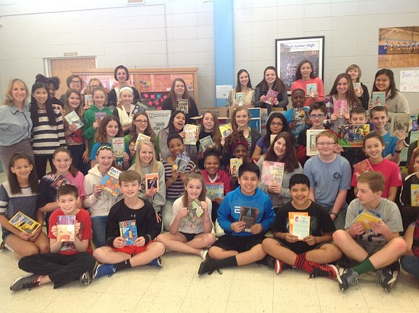 West Middle School students pose with books donated to the BrainFood program.