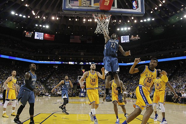 Minnesota Timberwolves' Andrew Wiggins (22) dunks against the Golden State Warriors during the second half of an NBA basketball game Tuesday, April 5, 2016, in Oakland, Calif. Minnesota won 124-117 in overtime. (AP Photo/Marcio Jose Sanchez)