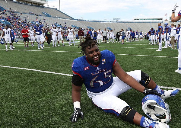Kansas offensive lineman Jayson Rhodes (65) picks himself off the ground after falling down laughing while fellow lineman field kickoffs during the Spring Game on Saturday, April 9, 2016 at Memorial Stadium.