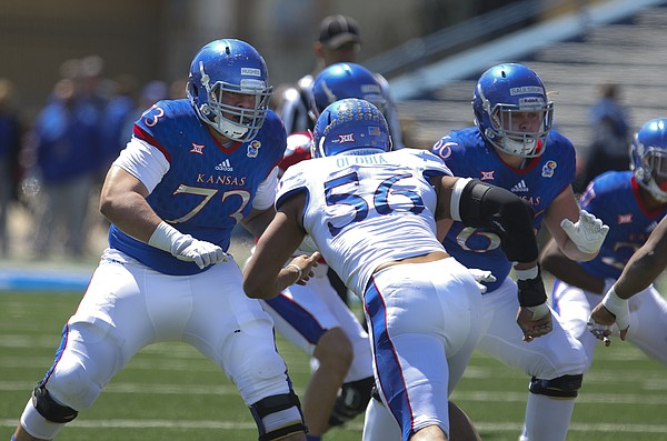 Kansas offensive lineman Larry Hughes (73) looks to fend off defensive end Anthony Olobia (56) during the Spring Game on Saturday, April 9, 2016 at Memorial Stadium.