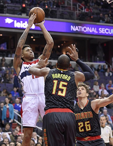 Washington Wizards forward Kelly Oubre Jr., left, takes a shot against Atlanta Hawks center Al Horford (15) and guard Kyle Korver (26) during the first half of an NBA basketball game, Wednesday, April 13, 2016, in Washington. (AP Photo/Nick Wass)