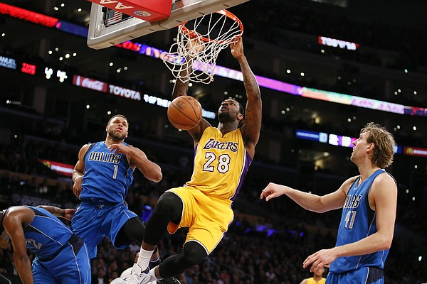 Los Angeles Lakers' Tarik Black dunks in front of Dallas Mavericks' Justin Anderson, left, and Dirk Nowitzki, right, during the second half of an NBA basketball game, Tuesday, Jan. 26, 2016, in Los Angeles. The Mavericks won 92-90. (AP Photo/Danny Moloshok)