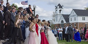 Wellsville High School students gather for group photos before cruising in their cars and walking with their dates through downtown. Shot with a 50mm lens, a lens often overlooked by photographers, the scene is captured in a similar perspective as seen with our unaided eyes.