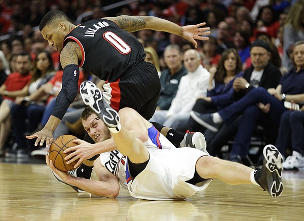 Los Angeles Clippers' Cole Aldrich, bottom, gets the ball against Portland Trail Blazers' Damian Lillard in the second half in Game 1 of a first-round NBA basketball playoff series Sunday, April 17, 2016, in Los Angeles. The Clippers won 115-95. (AP Photo/Jae C. Hong)