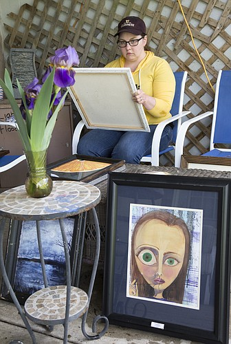 Cheyenne Bartz, shown here working on a painting at her Lawrence home, is one of approximately 100 artists showing work in Sunday's Art in the Park exhibition. The Lawrence Art Guild organizes the annual event, which will be be held from 10 a.m. to 5 p.m. on the east side of South Park.