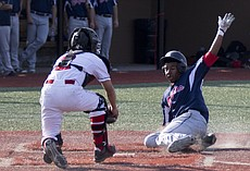 Olathe North senior Caleb Underwood slides into home plate, beating the tag by Lawrence High catcher Reese Carmona during their game Thursday afternoon at LHS. The Lions fell to the Eagles in eight innings, 3-2.