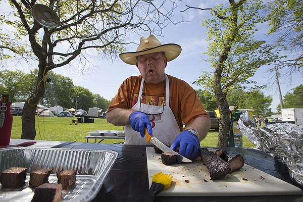 "Glynn Sheridan, with the ""Butts 'R' Us!"" team from Lawrence, carefully slices a cut of brisket as he prepares it for judging during the Lawrence Sertoma 48 BBQ Cookoff at Broken Arrow Park on Saturday, May 7, 2016."