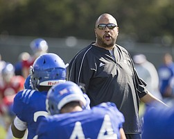 Kansas running backs coach Tony Hull encourages his players as they warm up during practice on Tuesday, April 5, 2016.