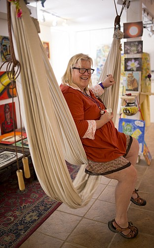 """Lawrence artist Linda Clark is pictured in a hammock she created as part of the """"We Can"""" show at the Lawrence Percolator, in the alley behind the Lawrence Arts Center on the 900 block of New Hampshire Street. Clark is one of six artists participating in the show, each of whom lives with mental illness."""