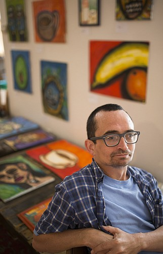"""Lawrence artist Sean Sullivan is pictured with some of his paintings featured as part of the """"We Can"""" show at the Lawrence Percolator, in the alley behind the Lawrence Arts Center on the 900 block of New Hampshire Street. The show features six artists, including Sullivan, who live with mental illness."""