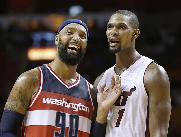 Washington Wizards forward Drew Gooden (90) and Miami Heat forward Chris Bosh (1) have a light moment in the second half of an NBA preseason basketball game, Wednesday, Oct. 21, 2015, in Miami. The Heat won 110-105. (AP Photo/Alan Diaz)