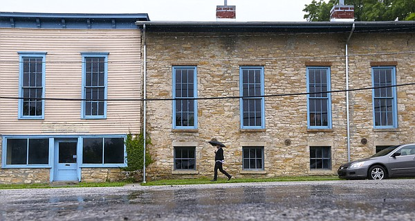 A pedestrian heads east on East Ninth Street past the Lawrence Turnhalle building, which is being looked at as a key element at play in the proposed East Ninth Street Project, Monday, May 23, 2016 at Ninth and Rhode Island streets. Lawrence developer, Tony Krsnich, who owns the Turnhalle building, has expressed frustration with what is perceived as the city's sluggishness in approving the project.