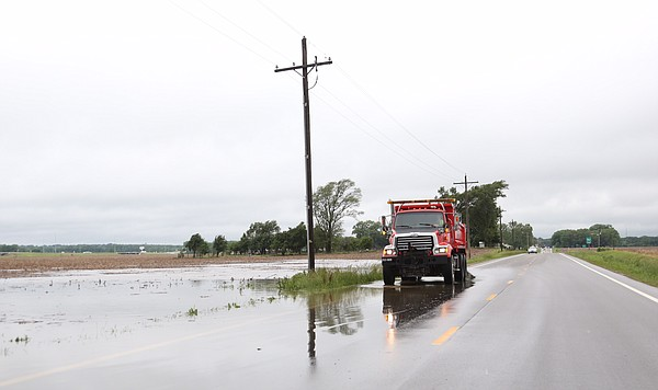 A Douglas County vehicle diverts traffic around standing water from flooding farm fields along U.S. Highway 24-40 near Airport Road, Friday morning, May 27, 2016.