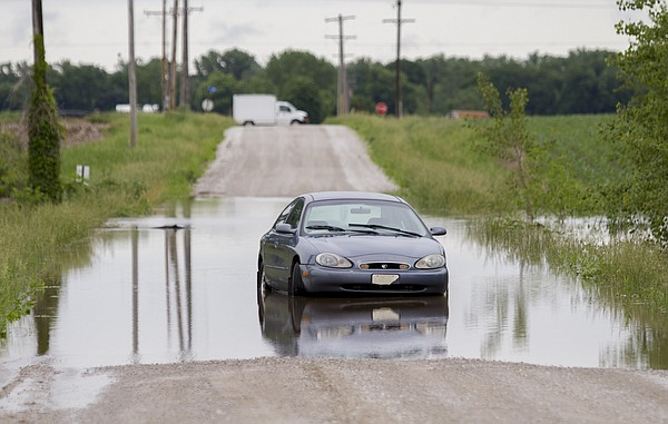 A car sits stranded in high water on East 1900 Road, north of North 1400 Road, Friday, May 27, 2016. Many fields were flooded and some roads in the area were partially covered with water after Thursday night storms.