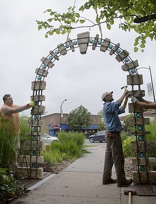 Lawrence sculptor John Rasmussen, right, works at installing his piece Blue and Gold, near South Park, with his friend Ty Hicklin, left, Tuesday, May 31, 2016.