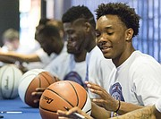 Kansas junior Devonte' Graham flashes a smile as he autographs a basketball during Bill Self Basketball Camp check-in on Sunday afternoon at Allen Fieldhouse.