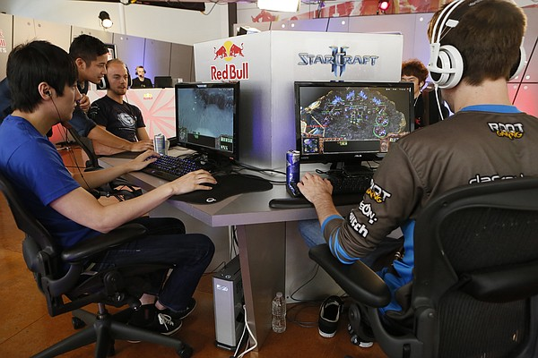 """In this photo taken Friday, June 21, 2013, Kyeong Hyun """"SeleCT"""" , left, joins seven of the world's best """"StarCraft II"""" video game players to train at Red Bull Training Grounds, held at Red Bull North America headquarters in Santa Monica, Calif. (AP Photo/Damian Dovarganes)"""