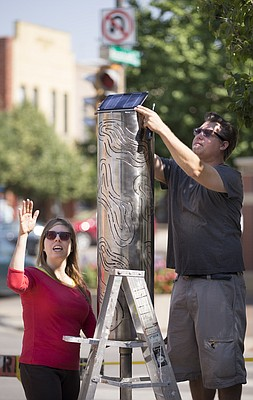 "Lawrence artists and husband and wife, Shannon and Darin White install their plasma-cut perforated steel sculpture, ""Soundshapes 2"" at the southeast corner of Ninth and Massachusetts streets on Friday, June 10, 2016. The sculpture, which has a solar-powered illuminating effect, is one of eight to be featured in the Downtown Outdoor Sculpture Exhibition."