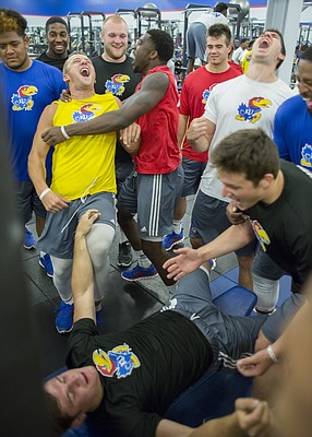 Kansas football team members react to a series of weightlifting reps by teammate Ryan Schadler during an early morning workout Friday morning, June 24, 2016.