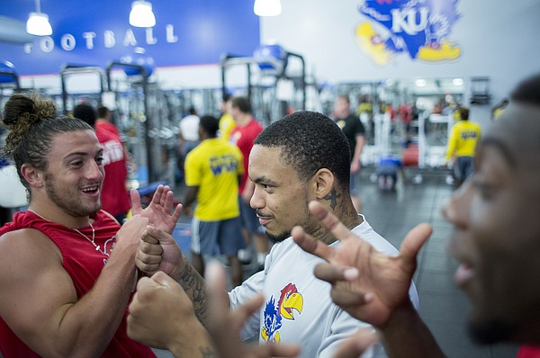 Kansas football teammates Keegan Brewer, left, and LaQuvionte Gonzalez, visit during weightlifting exercises Friday morning, June 24, 2016.