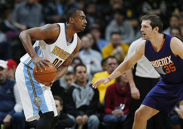 Denver Nuggets forward Darrell Arthur, left, looks to pass the ball as Phoenix Suns forward Mirza Teletovic, of Bosnia, defends in the first half of an NBA basketball game Thursday, March 10, 2016, in Denver. (AP Photo/David Zalubowski)