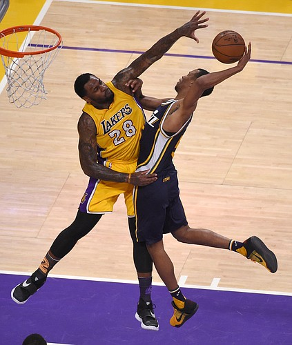 Los Angeles Lakers center Tarik Black, left, blocks the shot of Utah Jazz guard Rodney Hood during the second half of an NBA basketball game Wednesday, April 13, 2016, in Los Angeles. (AP Photo/Mark J. Terrill)