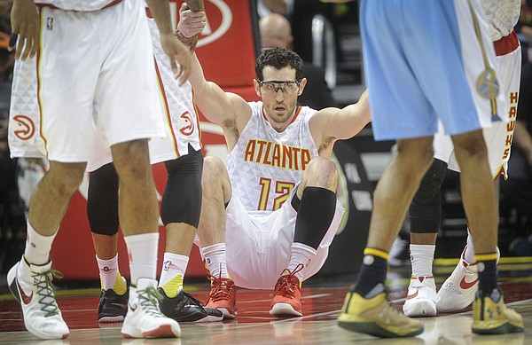 Atlanta Hawks guard Kirk Hinrich (12) is helped up after taking a charge against the Denver Nuggets during an NBA basketball game, Thursday, March 17, 2016, in Atlanta. Atlanta won 116-98.(AP Photo/John Amis)