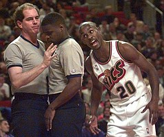Seattle SuperSonics' Gary Payton leans in to have a word with referees Michael Krom, left, and Leroy Richardson in the first quarter as Payton insists Seattle should have possession Tuesday, Dec. 5, 1995, in Seattle. Payton and teammates won the baseline call against the Toronto Raptors. (AP Photo/Elaine Thompson)