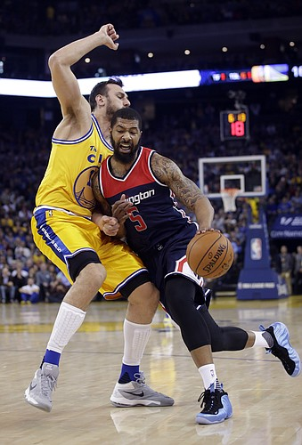 Washington Wizards' Markieff Morris (5) drives against Golden State Warriors' Andrew Bogut during the first half of an NBA basketball game Tuesday, March 29, 2016, in Oakland, Calif. (AP Photo/Marcio Jose Sanchez)