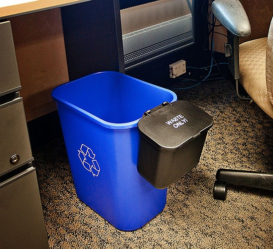 A photo of the new desk-side recycling and trash receptacles being put into use at Kansas University. (Photo courtesy of KU)