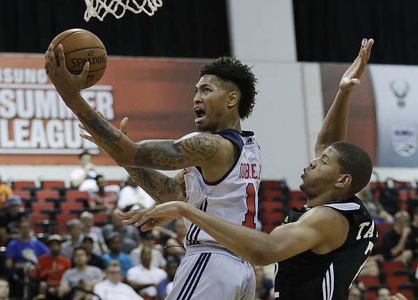 Washington Wizards' Kelly Oubre Jr., left, shoots around Atlanta Hawks' Edy Tavares during the first half of an NBA summer league basketball game, Sunday, July 10, 2016, in Las Vegas. (AP Photo/John Locher)