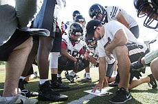 Lawrence High offensive coordinator Chris Johnson draws up some plays for players during LHS football camp on Monday July 11, 2016.