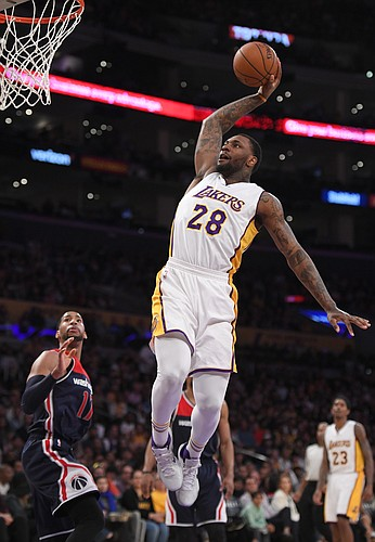 Los Angeles Lakers center Tarik Black, right, tries to dunk and misses as Washington Wizards guard Garrett Temple defends during the second half of an NBA basketball game, Sunday, March 27, 2016, in Los Angeles. The Wizards won 101-88. (AP Photo/Mark J. Terrill)