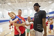 One-year-old Landley Sheppard is a little too shy to meet Andrew Wiggins as she is carried over by her father Mark Sheppard during Wiggins' and Ben McLemore's Kansas All-Star Basketball Camp on Thursday, July 14, 2016 at Sports Pavilion Lawrence. At center is Heather Sheppard.