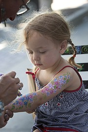 Two-year-old Leona Richardson, of Lawrence, watches as she has flowers painted on her arm at the Sidewalk Sale in downtown Lawrence on Thursday, July 21, 2016.