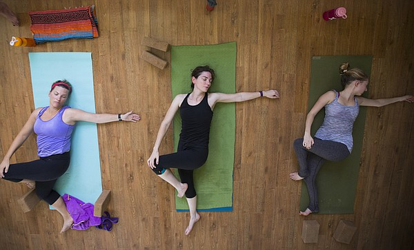 Hot Hatha yoga students lie on their backs as they perform some final stretches before the end of class on Friday, July 22, 2016 at OmTree Shala, 1405 Massachusetts St.
