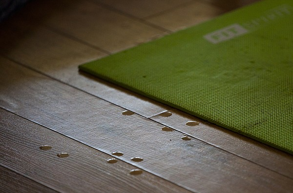 Drops of sweat gather off the side of a yoga mat.