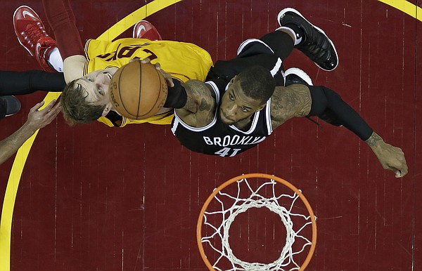 Cleveland Cavaliers' Timofey Mozgov, left, from Russia, and Brooklyn Nets' Thomas Robinson battle for a rebound in the second half of an NBA basketball game Thursday, March 31, 2016, in Cleveland. (AP Photo/Tony Dejak)