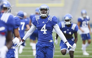 Kansas receiver Daylon Charlot soars back to get in line during team stretches at the beginning of practice on Monday, Aug. 15, 2016 at Memorial Stadium.