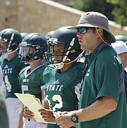 Free State sophomore quarterback Jordan Preston (12) discusses plays with co-offensive coordinator Adam Barmann, right, during the football team's preseason scrimmage on Saturday, August 20.