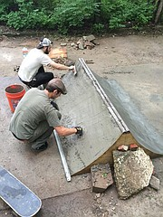 Members of Lawrence Skaters Association work on a ramp at the Riverside DIY Skate Park.