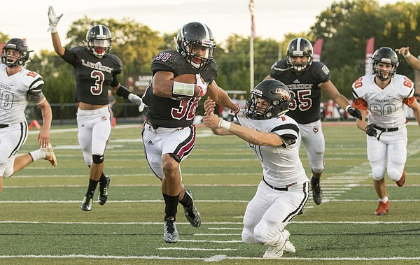 Lawrence High senior running back Trey Moore (38) gives Shawnee Mission Northwest defensive back Caleb Johnson (7) a stiff arm as he breaks away to score one of his four touchdowns during their game on Friday night at LHS. The Lions jumped out to a 23-0 first quarter lead and never looked back as they defeated the Cougars, 50-20.