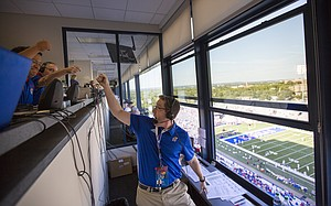 Brian Hanni salutes his coworkers in the booth shortly before his first football broadcast as the voice of the Jayhawks on Saturday, Sept. 3, 2016 at Memorial Stadium.