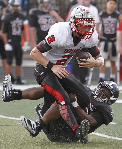 James Murray (19) right, sacks Shawnee Mission North quarterback Will Schneider in the Lawrence Lions win against Shawnee Mission North Friday night at LHS.