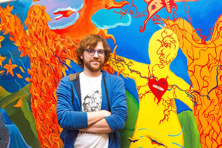 "Lance LeClair helped to paint the autumn section of the ""Life Changes"" mural."